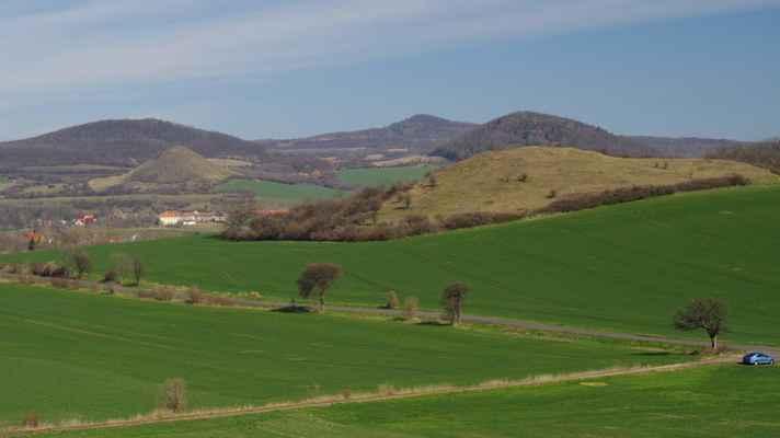vlevo za libčevsí se tyčí kamýk, za ním je hradišťko, uprostřed na obzoru je ostrý, vpravo vpředu je travnatý mlýnský vrch a za ním křížový vrch...