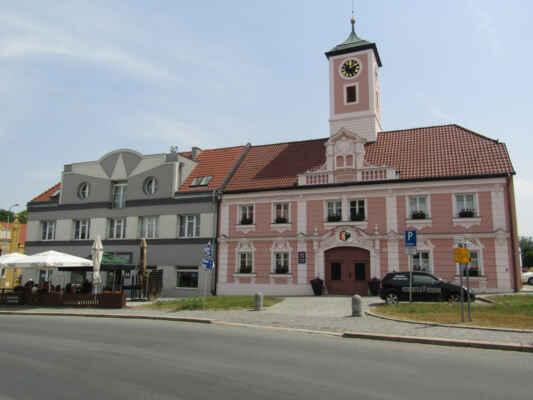 """Městská radnice byla polovině 19. století postavena na náměstí z domu, který městu prodal bývalý rychtář Matěj Šmolík. Na průčelí radnice je umístěn znak města s latinským nápisem s latinským nápisem ( vlastně opisem gotickou majuskulí) SIGILLUM OPPIDI ANTIQUAE PILSNAE čili """" znak města Staré Plzně"""". Uprostřed je městský znak již na barokním štítu s černou orlicí a bílým dvouocasým lvem."""