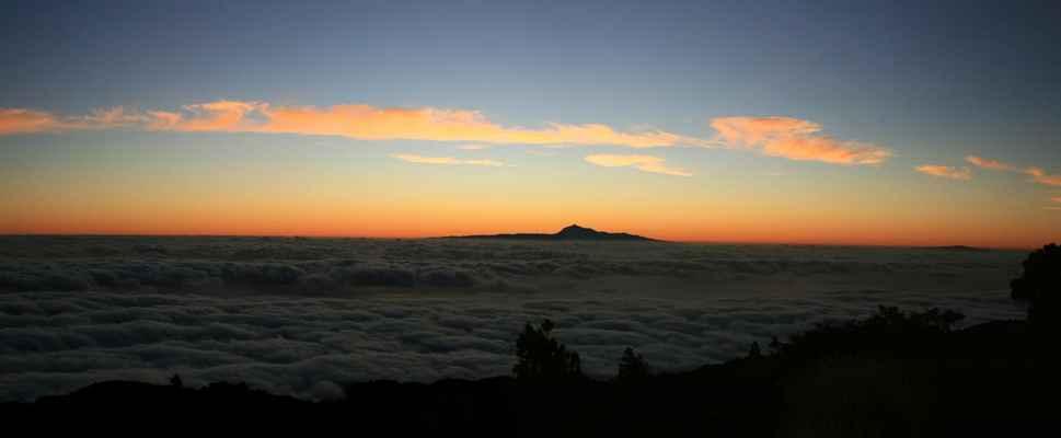...blížíme se ke hřebeni, mraky zůstávají dole, Pico del Teide (3718 m.n.m.) na Tenerife, vpravo ostrov La Gomera...
