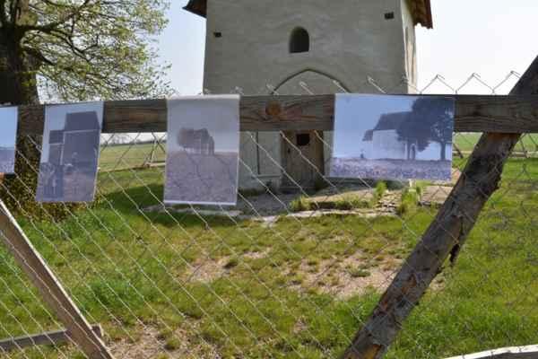 Na plote okolo kapličky-kostolíka sú povešané retro fotografie.